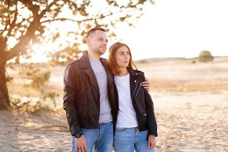 Happy and cute adorable adult couple leather jacket and jeans man with woman girlfriend walking, have fun play, laugh,smile and jump on sunset at desert crazy in love, emotions and relationship Foto de archivo