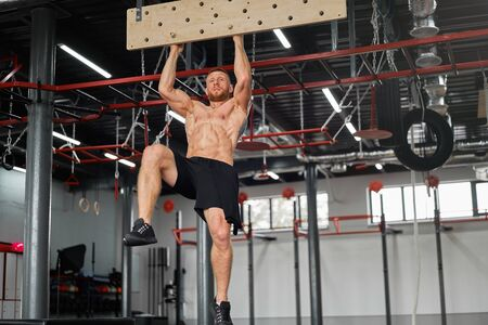 Man climbing pegboard gym athlete training arm strength stamina alpinism indoor. Athlete caucasian guy hanging from his hands wooden campus board warming up to climb Functional Cross training workout