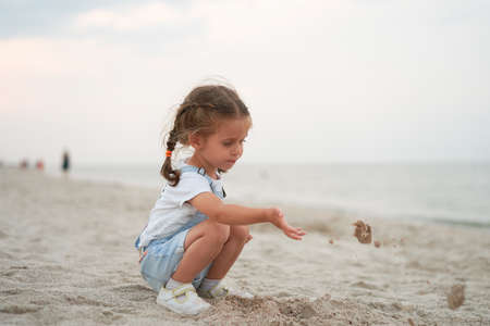 Child playing sand beach Little girl play sad alone summer family vacation Caucasian female 3 years old dressed denim near sea water