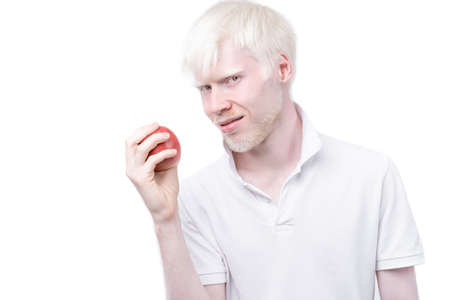 albinism albino man white skin hair studio dressed t-shirt isolated white background. abnormal deviations. unusual appearance. skin abnormality Beautiful people with special appearance. Eat red apple