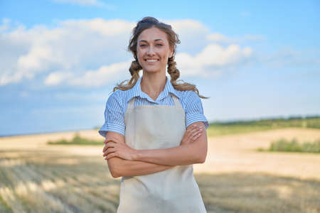 Woman farmer apron standing farmland smiling Female agronomist specialist farming agribusiness Happy positive caucasian worker agricultural field Pretty girl arms crossed cloudy sky background