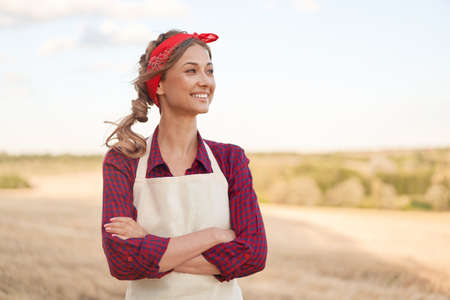 Woman farmer apron standing farmland smiling Female agronomist specialist farming agribusiness Happy positive caucasian worker agricultural field Pretty girl arms crossed dressed red checkered shirt