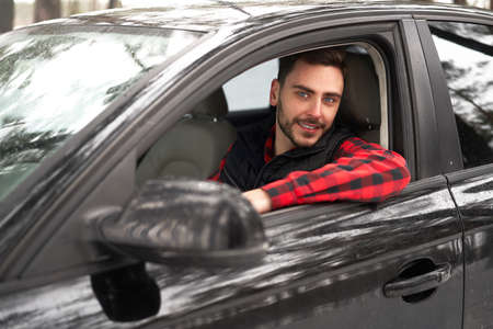 Young adult attractive Caucasian man sits at the wheel of his car sunny winter day. Wintertime road trip. Happy smiling hipster guy sitting in car and looking window. Portrait Positive driver