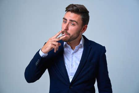 Businessman Business person. Man business suit studio gray background. Modern business person stylish haircut smokes a cigarette Portrait of charming successful young entrepreneur Foto de archivo