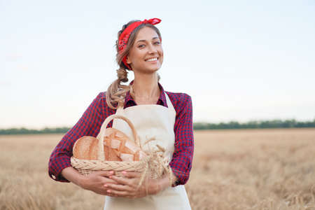 Female farmer standing wheat agricultural field Woman baker holding wicker basket bread eco product Baking small business Caucasian person dressed red checkered shirt apron organic healthy food Foto de archivo