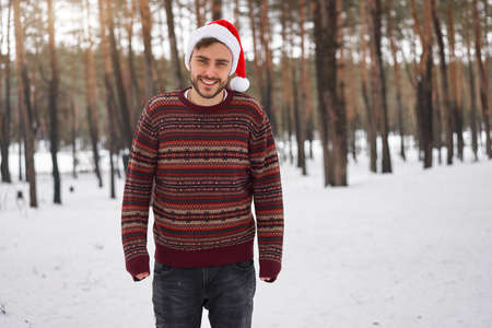 Handsome bearded young caucasian man standing outdoors sweater santa hat winter season forest. Attractive stylish european guy walking snowy christmas woodland Season holiday leisure