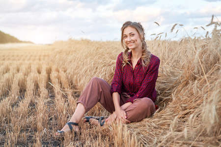 Woman farmer sitting farmland smiling Female agronomist specialist farming agribusiness Happy positive caucasian worker agricultural field dressed red checkered shirt and bandana Red plaid shirt.