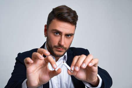 Businessman Business person. Man business suit studio gray background. Modern person breaks a cigarette stopped smoking Portrait of charming successful young entrepreneur Foto de archivo