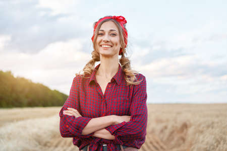 Woman farmer standing farmland smiling Female agronomist specialist farming agribusiness Happy positive caucasian worker agricultural field dressed red checkered shirt and bandana arms crossed Foto de archivo