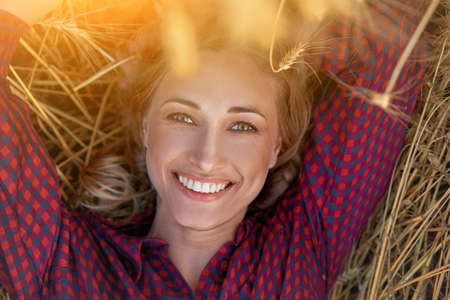 Woman farmer lie farmland smiling Female agronomist specialist farming agribusiness Happy positive caucasian worker agricultural field dressed red checkered shirt and bandana Red plaid shirt.
