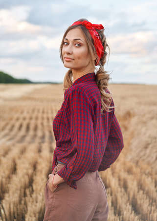 Woman farmer standing farmland smiling Female agronomist specialist farming agribusiness Happy positive caucasian worker agricultural field dressed red checkered shirt and bandana Foto de archivo
