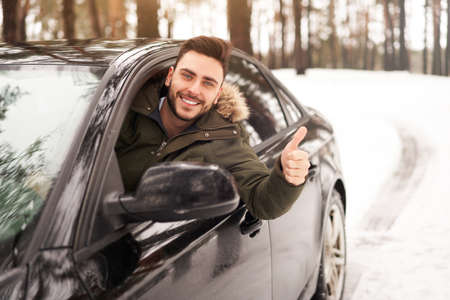Young adult attractive Caucasian man sits at the wheel of his car sunny winter day shoeing thumbs up gesture. Wintertime road trip. Happy smiling hipster guy sitting in car and looking window. Foto de archivo