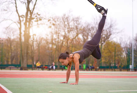 Girl athlete training . young adult woman workout suspension system Healthy lifestyle Stretching outdoors playground. Make your body machine