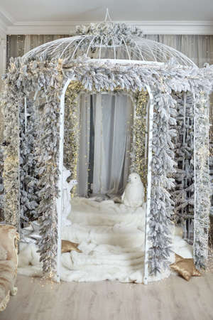 Big white decorative cage decorated chrismas tree light garland artificial snow and toy white bear place phot festive photo Nobody Photo studio Foto de archivo