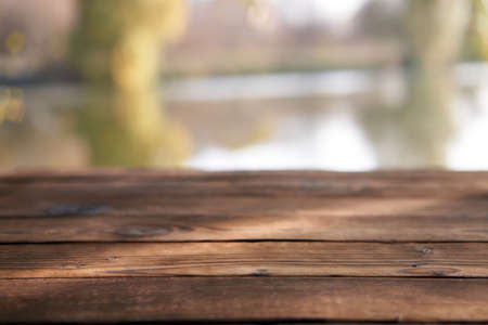Empty wooden table nature bokeh background with a country outdoor theme, Template mock up for display of product Copy space Lake