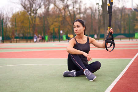 race young adult woman workout suspension system Healthy lifestyle Stretching outdoors playground.