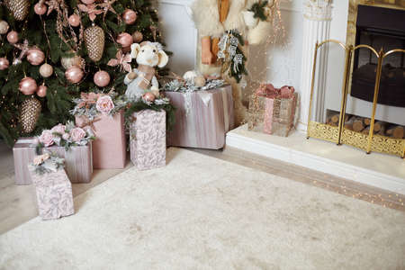 Christmas gift box under Chrismas tree lies on white carpet near fireplace Holiday morning. New year present paper package. Festive mood Foto de archivo