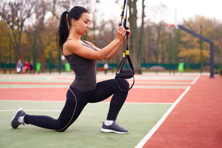 Girl athlete training   sportground Mixed race young adult woman workout suspension system Healthy lifestyle Stretching outdoors playground. Make your body machine Foto de archivo