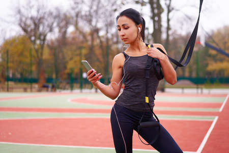 Girl athlete training  sportground Mixed race young adult woman workout suspension system Healthy lifestyle Stretching outdoors playground. Make your body machine