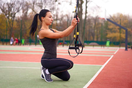 young adult woman workout suspension system Healthy lifestyle Stretching outdoors playground. Make your body machine Foto de archivo