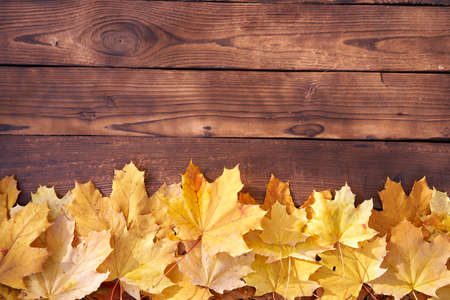 Autumn leaves frame on wooden background top view Fall Border yellow and Orange Leaves vintage wood table Copy space for text