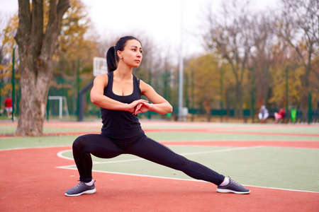 Happy girl doing fitness exercises outdoor on playground. Healthy lifestyle. Morning workout positive emotion smiling sportive people. one female training stretching Foto de archivo