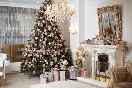 Christmas tree standing living room interior near fireplace gift box lie on carpet near evergreen fir Christmas time. Norning holidays