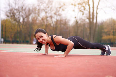Happy girl doing plank outdoor on playground. Healthy lifestyle. Morning workout positive emotion smiling sportive people. one female training Foto de archivo