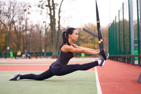 young adult woman workout suspension system Healthy lifestyle Stretching outdoors playground. Foto de archivo