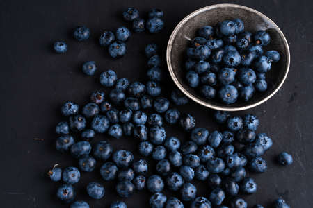 Blueberry antioxidant organic superfood in ceramic bowl concept for healthy eating and dieting nutrition Top view on dark black background Zdjęcie Seryjne