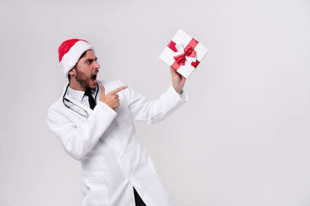 Young handsome doctor in white uniforme and Santa hat in studio white background smile Shows a finger at the gift box. showing thumbs up Medical student Christmas New Year Holiday Medicine concept