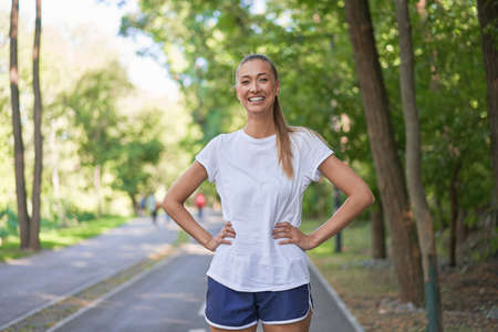 Woman runner standing before exercising summer park morning Middle age athletic female warming up body before running Caucasian person warm up jogging Dressed white shirt shorts running track
