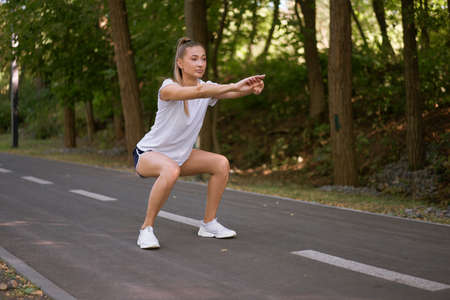 Woman runner stretching legs before exercising summer park morning Middle age athletic female warming up body before running Caucasian person warm up jogging Dressed white shirt shorts running track