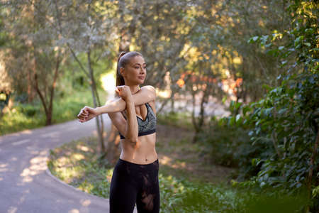 Woman runner stretching arms before exercising summer park morning Middle age athletic female warming up body before running Caucasian person warm up jogging running track 免版税图像