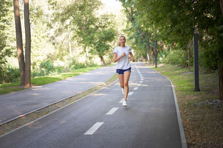 Woman running asphalt road summer park Active sporty caucasian female morning workout Healthy lifestyle concept. Athletic person sportswear exercises Dressed white t-shirt full length 免版税图像