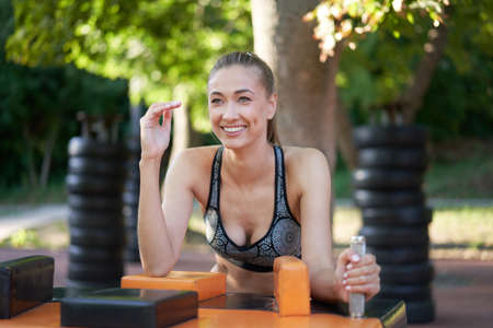 Sportive female arm wrestling outdoor gym summer park Middle age caucasian woman dressed sportswear workout outside on simulator sport ground. Healthy lifestyle concept 免版税图像