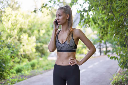 Woman runner standing before exercising summer park morning Middle age athletic female warming up body before running Caucasian person Talking on the phone. running track