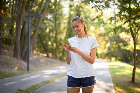Woman putting on earphones to listen music before jogging summer park Caucasian female preparing to run sunny morning Runner ready training holdin smartphone hand Healthy lifestyle positive concept 免版税图像