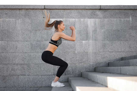 Urban sporty woman training. Female athlete doing squat jumps on urban stairs. Fitness motivation Healthy lifestyle concept 免版税图像