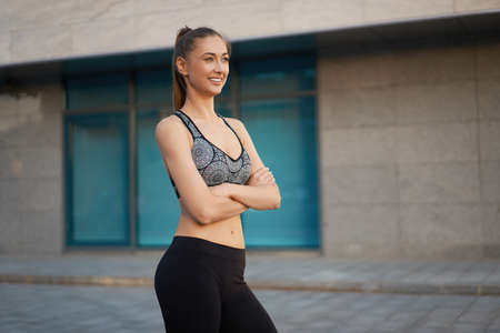 Woman runner standing before exercising urban city background Middle age athletic female before running Caucasian person tunes in for training Posing Corporate building windows