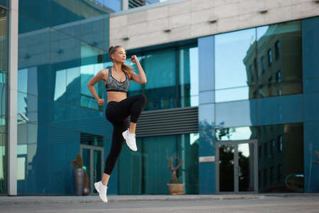 Woman with fit body jumping and running against urban city background. Female model in sportswear exercising outdoors. Sport motivation Healthy lifestyle concept Corporate building window full length 免版税图像