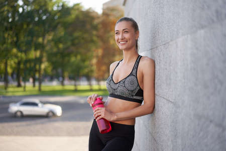 Tired Woman drink water red bottle after morning workout Young athletic female rear view standing leaning wall city street park background after jogging Healthy lifestyle concept Copy space