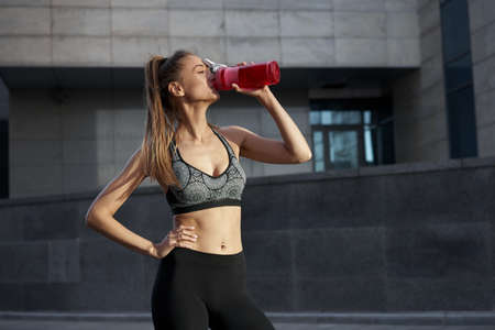 Tired Woman drink water red bottle after morning workout. Young athletic female standing city street background after jogging Healthy lifestyle concept