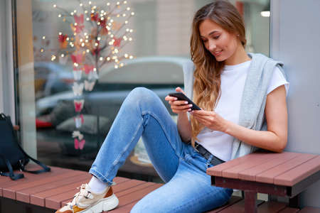 Woman city street summer sitting bench smartphone showcase shop window outdoor Modern stylish travel girl with backpack resting happy smiling Middle age female alone chatting mobile cell phone