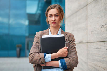 Businesswoman successful woman business person standing outdoor corporate building exterior Pensive elegance cute caucasian confidence professional business woman holding folder documents Bank worker