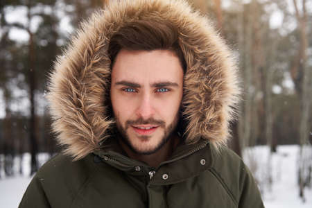 Handsome bearded young caucasian man standing outdoors fur hood in winter season forest. Attractive stylish european guy walking snowy christmas woodland Season holiday leisure 免版税图像