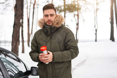 Attractive Caucasian man stands winter forest near car drink hot beverage thermos. Winter holiday road trip. Cold season. Portrait young handsome unshaved driver. Modern hipster guy traveling on car