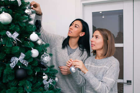 Two young women decorate the Christmas tree, preparing for the New Year's celebration. Friends decorate a Christmas tree. Beautiful girls are smiling and have fun during the Christmas holidays.
