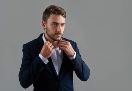 Businessman Business person. Man business suit studio gray background. Modern business person straightens shirt collar Portrait of charming successful young entrepreneur 免版税图像