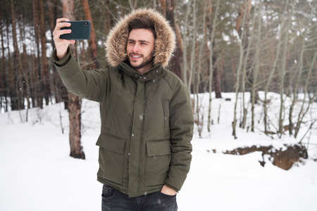 Handsome bearded young caucasian man standing outdoors fur hood winter forest Happy smiling Attractive stylish european guy walking taking selfie on smartphone Photograph Blogger Winter adventure